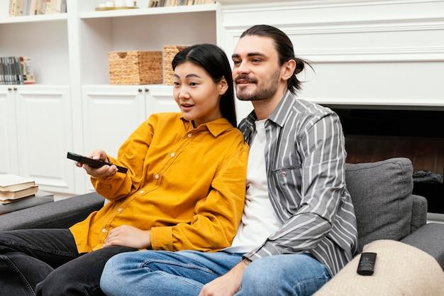 Vista lateral de casal sentado no sofá assistindo tv Foto gratuita