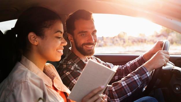 Vista lateral de casal viajando de carro Foto gratuita