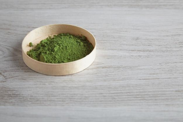 Vista lateral de chá matcha orgânico premium em pó em uma caixa de madeira isolada na mesa branca simples Foto gratuita