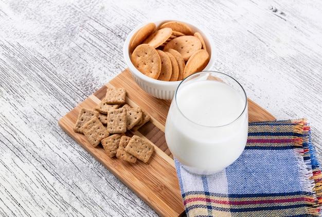 Vista lateral de cookies com leite na mesa de madeira horizontal Foto gratuita