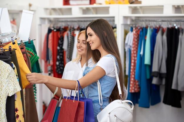 Vista lateral de duas mulheres escolhendo roupas novas no shopping Foto Premium