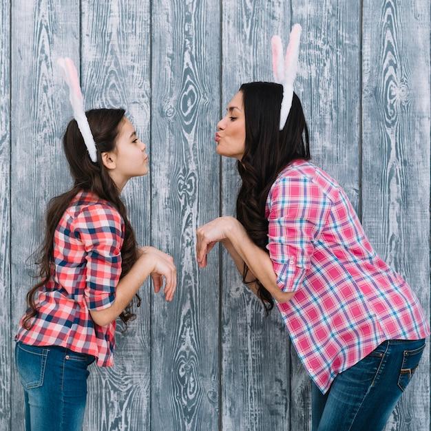 Vista lateral, de, filha, e, mãe, posar, como, um, coelho, pouting, contra, cinzento, madeira, fundo Foto gratuita