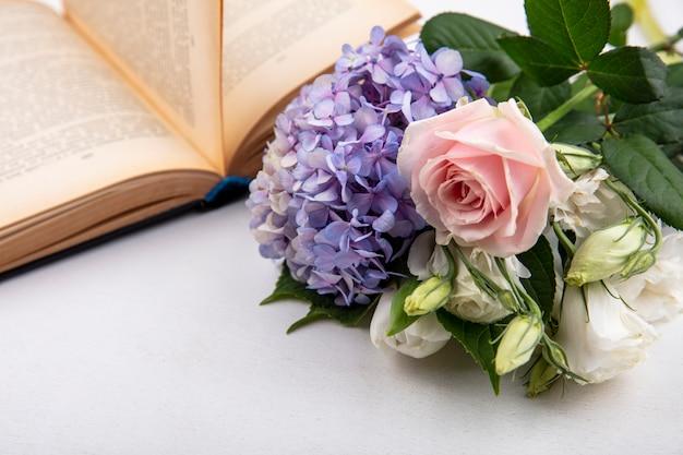 Vista lateral de flores com livro aberto em fundo branco Foto gratuita
