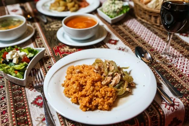 Vista lateral de frango frito com cebola bulgur e salada de legumes com sopa na mesa Foto gratuita