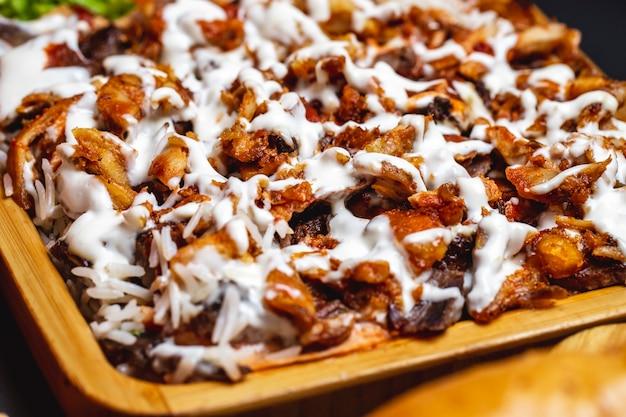 Vista lateral de frango grelhado com maionese e guarnição de arroz em uma bandeja Foto gratuita