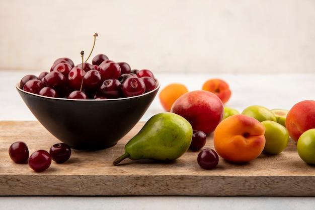 Vista lateral de frutas como pêssego, ameixa e pêssego com tigela de cereja na tábua de cortar Foto gratuita