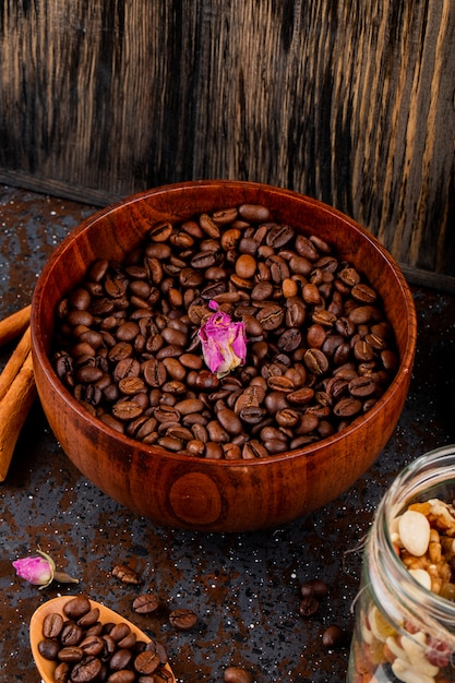 Vista lateral de grãos de café torrados em uma tigela de madeira em fundo preto Foto gratuita