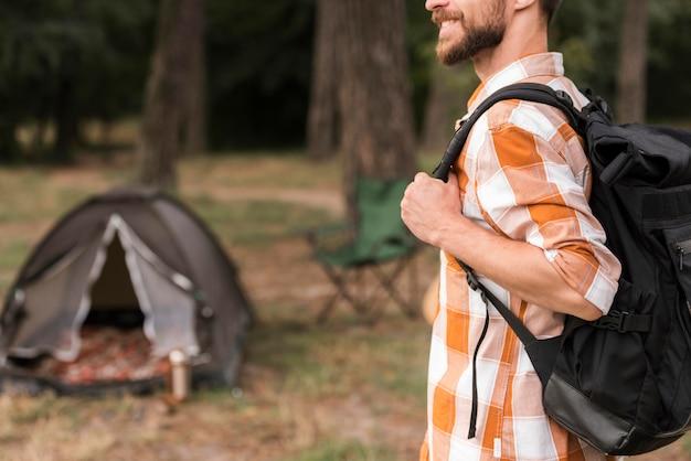 Vista lateral de homem com mochila e acampamento com barraca Foto gratuita