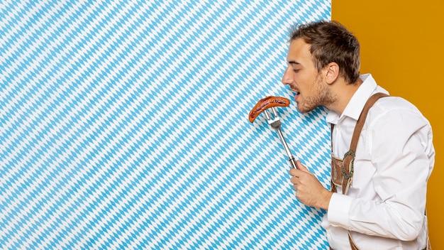 Vista lateral, de, homem, comer, linguiça Foto gratuita