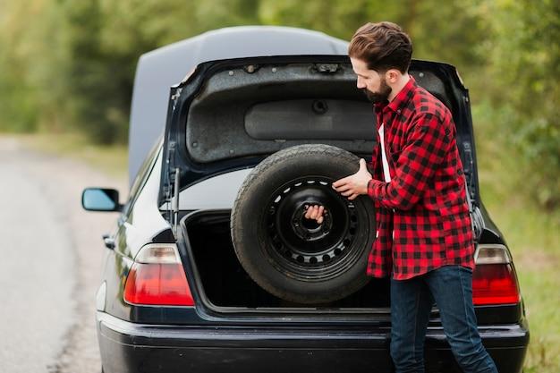 Vista lateral, de, homem, segurando, sobressalente, pneu Foto gratuita