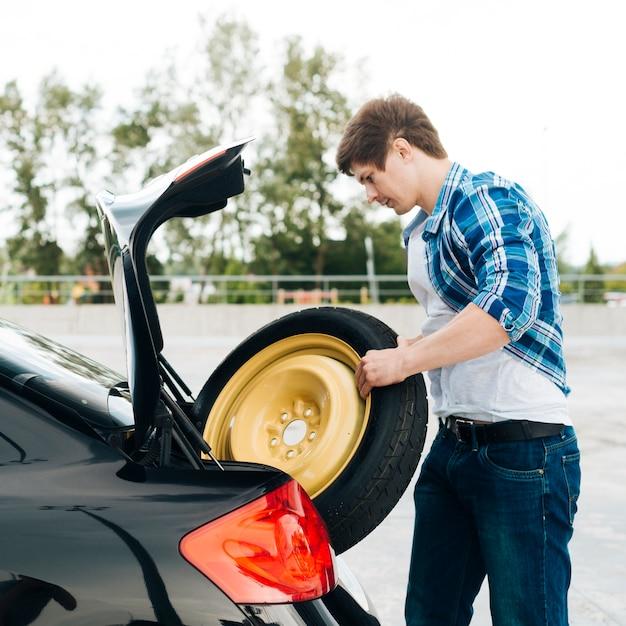 Vista lateral, de, homem, tirando, sobressalente, pneu Foto gratuita