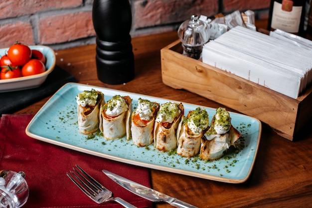 Vista lateral de lavash rola com molho azedo de legumes e pistache em uma mesa de madeira Foto gratuita