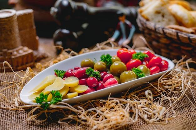 Vista lateral de legumes em conserva tomates pepinos e dogwood em um prato fundo de palha Foto gratuita