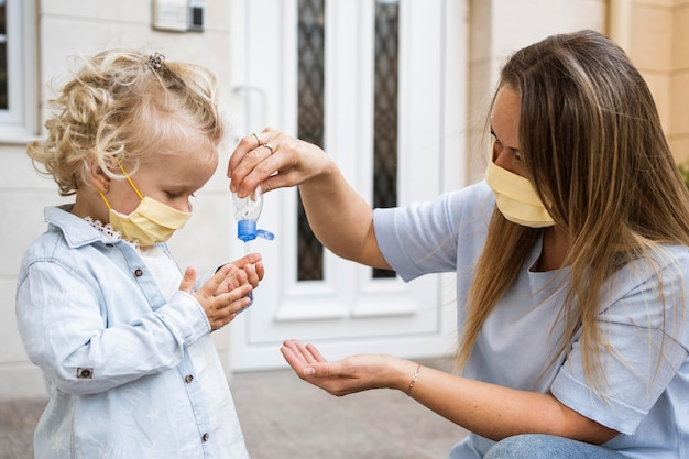 Vista lateral de mãe e filho com máscaras médicas e desinfetante para as mãos Foto gratuita