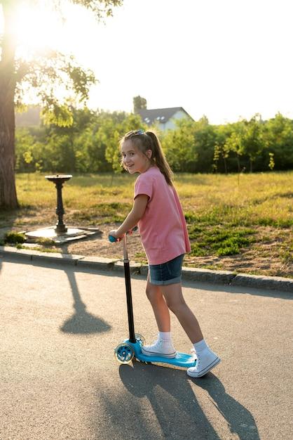 Vista lateral, de, menina, ligado, azul, scooter Foto gratuita