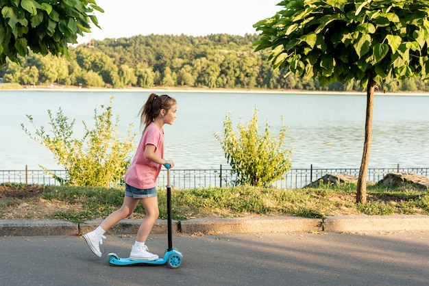 Vista lateral, de, menina, montando, azul, scooter Foto gratuita