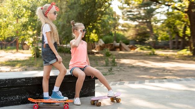 Vista lateral, de, meninas, com, skates Foto gratuita