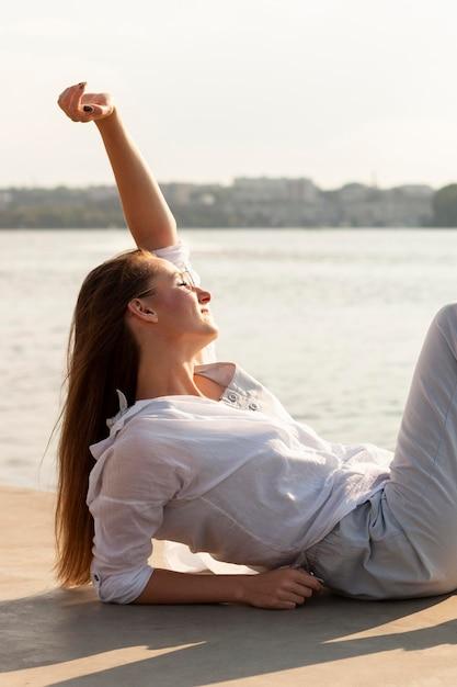 Vista lateral de mulher curtindo o sol à beira do lago Foto gratuita