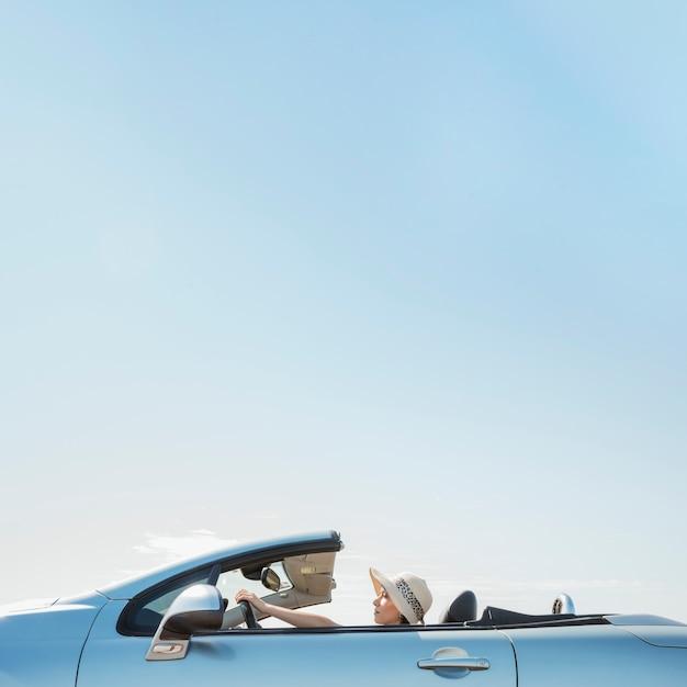 Vista lateral, de, mulher, dirigindo, cabriolet Foto gratuita