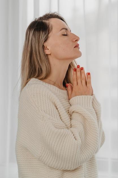 Vista lateral de mulher orando em casa Foto Premium