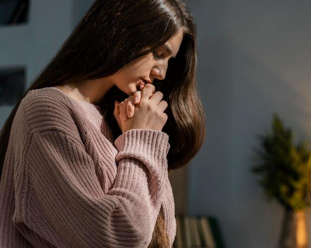 Vista lateral de mulher orando Foto gratuita