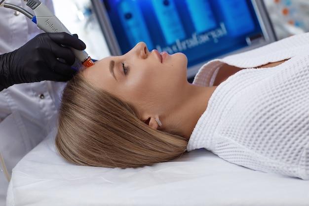 Vista lateral de mulher recebendo terapia de microdermoabrasão na testa no spa de beleza. procedimento hidrafacial em clínica de cosmetologia. Foto Premium