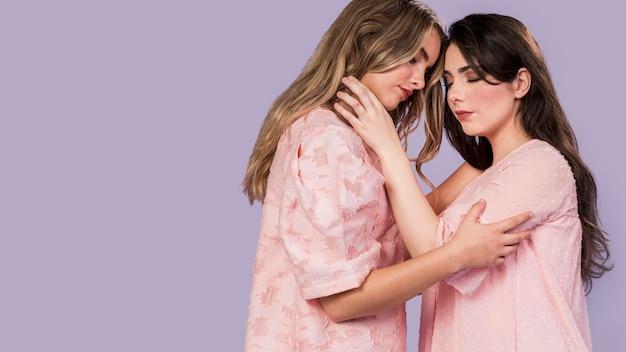 Vista lateral de mulheres abraçadas Foto gratuita