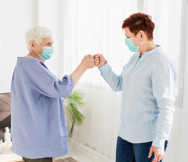 Vista lateral de mulheres mais velhas, batendo os punhos enquanto usava máscaras médicas Foto gratuita
