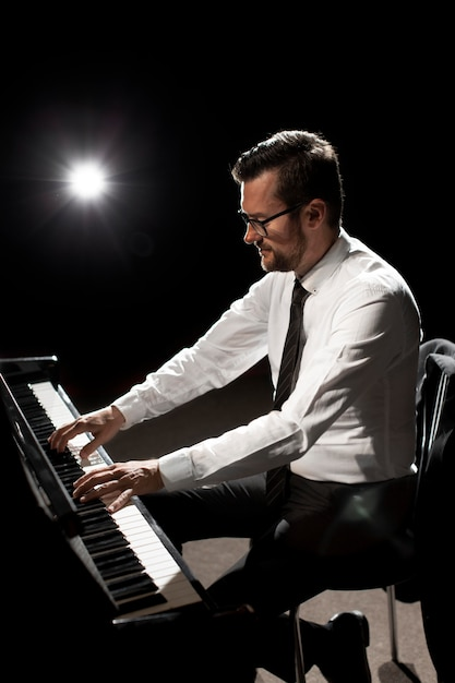 Vista lateral de músico tocando piano Foto gratuita