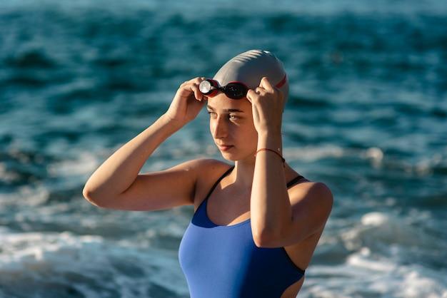 Vista lateral de nadadora com boné e óculos de natação Foto gratuita