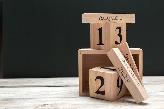 Vista lateral de partes do calendário de madeira na mesa de madeira escura Foto Premium