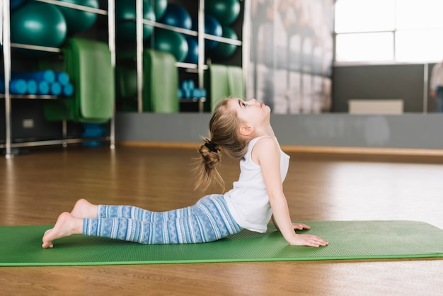 Vista lateral, de, pequeno, menina, prática, ioga, para, vida saudável Foto gratuita