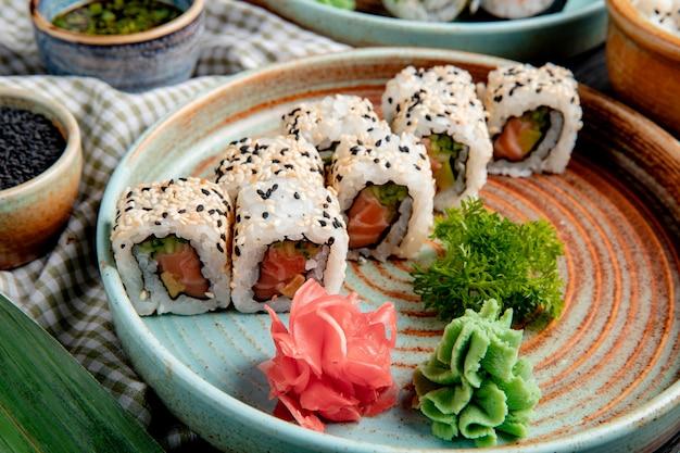 Vista lateral de rolos de sushi com atum salmão e abacate coberto com gergelim em um prato com wasabi e gengibre Foto gratuita