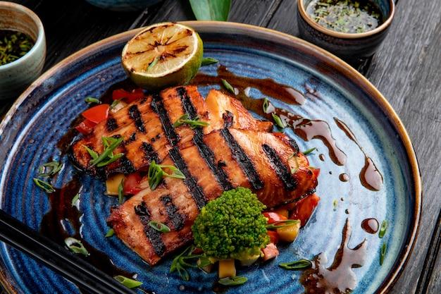 Vista lateral de salmão grelhado com legumes limão e molho de soja em um prato na mesa de madeira Foto gratuita