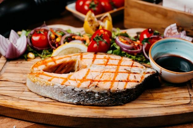 Vista lateral de salmão grelhado servido com legumes e molho na placa de madeira Foto gratuita
