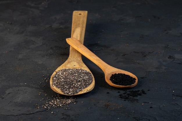 Vista lateral de sementes de cominho preto em colheres de pau no preto Foto gratuita