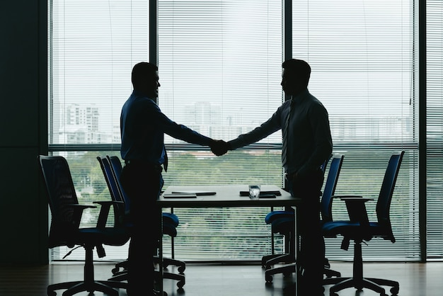 Vista lateral de silhuetas de dois homens irreconhecíveis, apertando as mãos no escritório Foto gratuita
