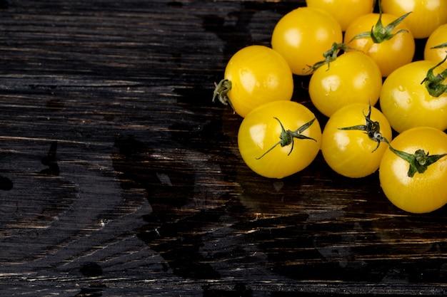 Vista lateral de tomates amarelos na madeira com espaço de cópia Foto gratuita