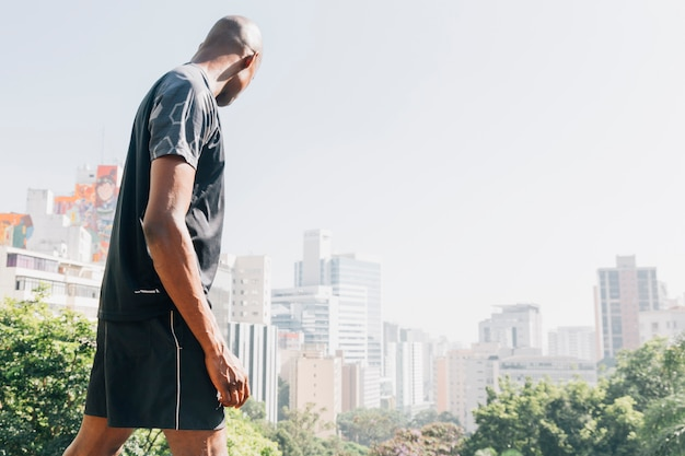 Vista lateral, de, um, atleta, homem jovem, olhar, horizonte cidade Foto gratuita