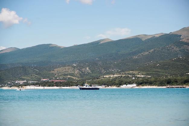 Vista lateral de um barco pesqueiro sem pessoas na baía do mar negro na praia Foto Premium