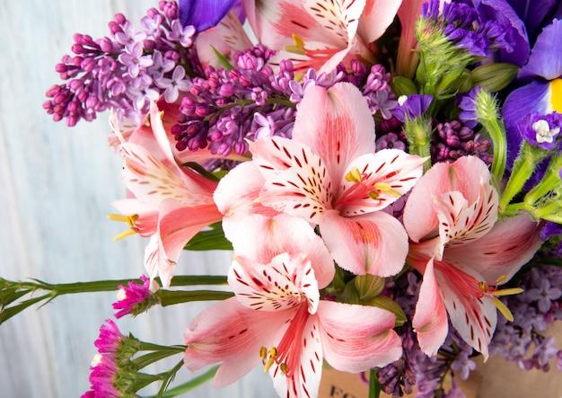 Vista lateral de um buquê de flores cor de rosa e roxo alstroemeria lilás íris e statice em papel ofício em fundo branco de madeira Foto gratuita