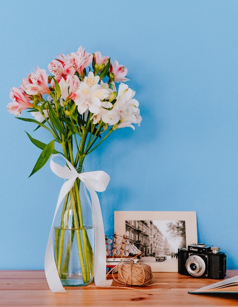 Vista lateral de um buquê de flores de alstroemeria cor de rosa e branco em um vaso de vidro com câmera antiga de foto emoldurada e novelo de corda em uma mesa de madeira no fundo da parede azul Foto gratuita