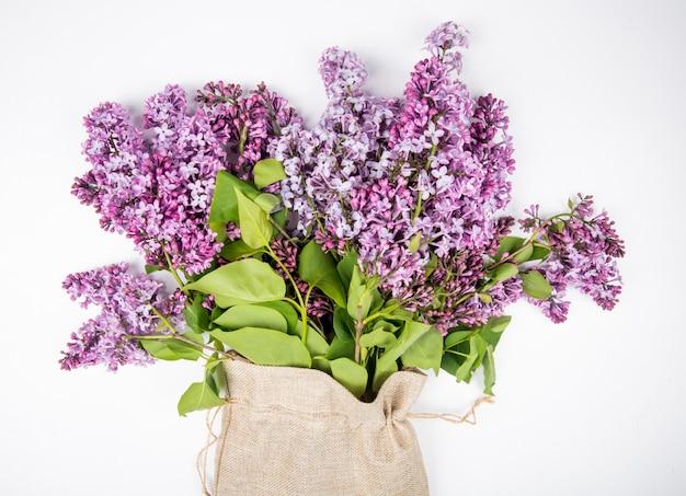 Vista lateral de um buquê de flores lilás em um saco em fundo branco Foto gratuita