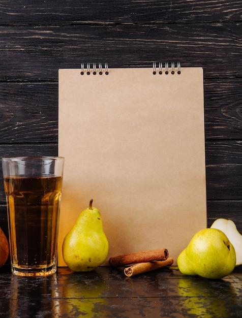 Vista lateral de um caderno de desenho e peras maduras frescas com um copo de suco de pêra em fundo de madeira Foto gratuita