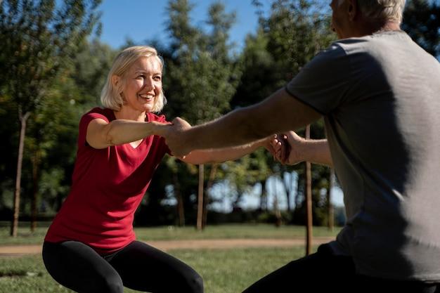 Vista lateral de um casal de idosos fazendo exercícios ao ar livre Foto gratuita