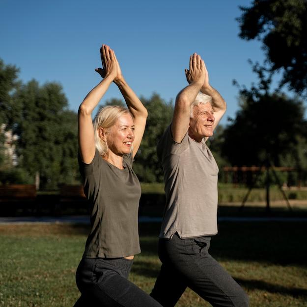 Vista lateral de um casal de idosos fazendo ioga ao ar livre Foto Premium