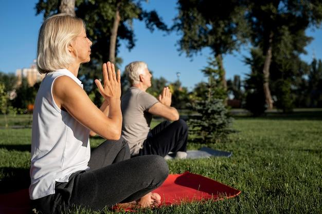 Vista lateral de um casal mais velho praticando ioga ao ar livre com espaço de cópia Foto gratuita