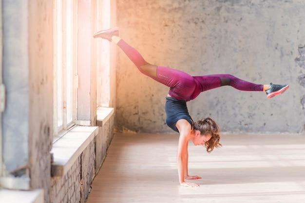 Vista lateral, de, um, condicão física, mulher jovem, fazendo, handstand, com, divisões Foto gratuita