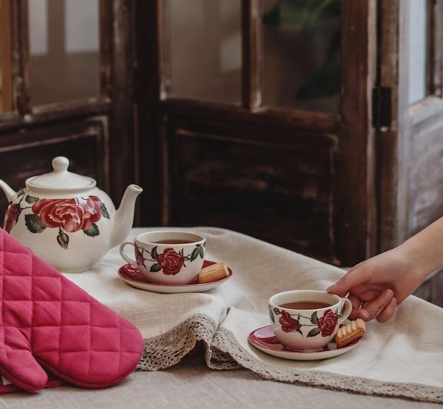 Vista lateral de um conjunto de chá de padrão floral rosa com um bule de chá e uma xícara de chá com biscoitos na toalha da mesa Foto gratuita