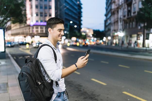Vista lateral de um homem feliz olhando para smartphone Foto gratuita